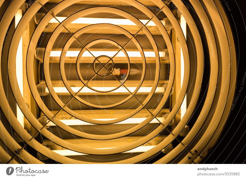 An old light bulb in the middle of fluorescent tubes abstract Art backdrop Background backgrounds built structure ceiling ceiling light circle creative