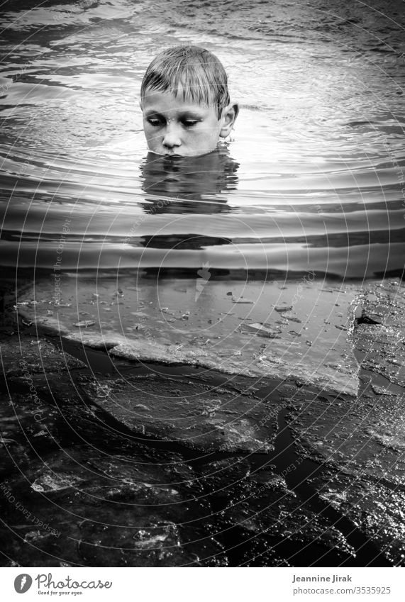 Boy bathes in icy water Boy (child) Water Lake Ice Swimming & Bathing Float in the water Waves Black & white photo Reflection vacation silent silence Monochrome