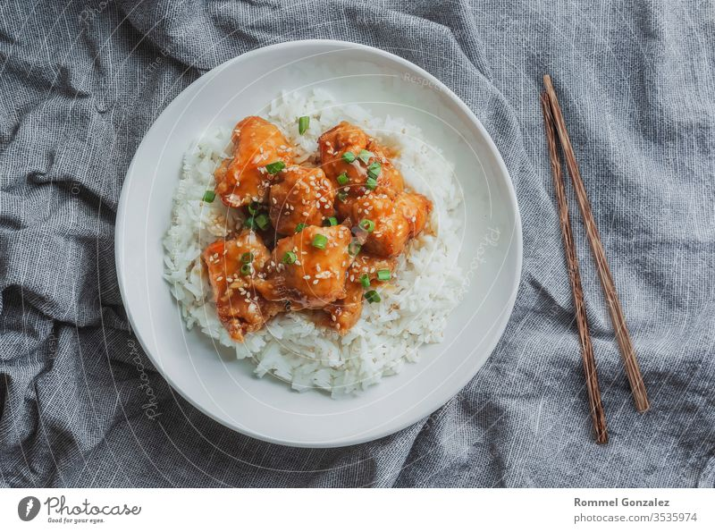 Delicious chicken with sweet and sour orange sauce accompanied by jasmine rice Chinese-style recipe, top view. cookery bowl table chili prepared basmati