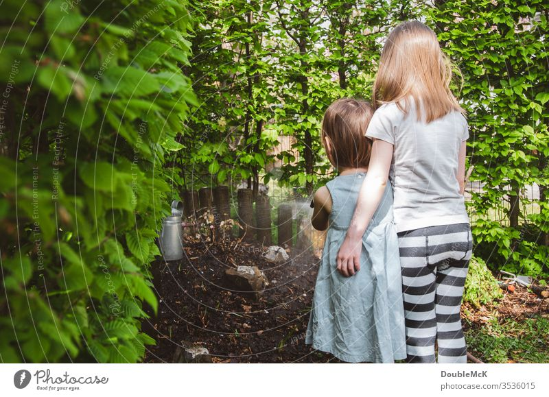 Two children watering the garden hugging girl Colour photo Cast Embrace at the same time Attachment Affection Leisure and hobbies Garden Gardening Hedge