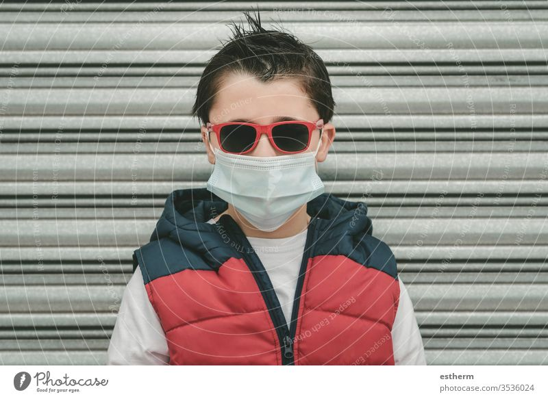 kid wearing medical mask for coronavirus with sunglasses child epidemic pandemic quarantine covid-19 symptom medicine health childhood protection cool summer