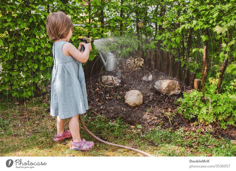 A girl waters the garden Colour photo Cast Leisure and hobbies Garden Gardening Hedge muck about Engagement engaged green Water hose Exterior shot Day Hose