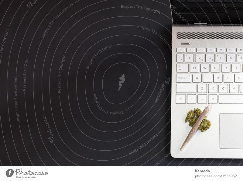 Marijuana and technology background. Cannabis buds and marijuana joint on laptop isolated on black background with copy space left. cannabis computer weed