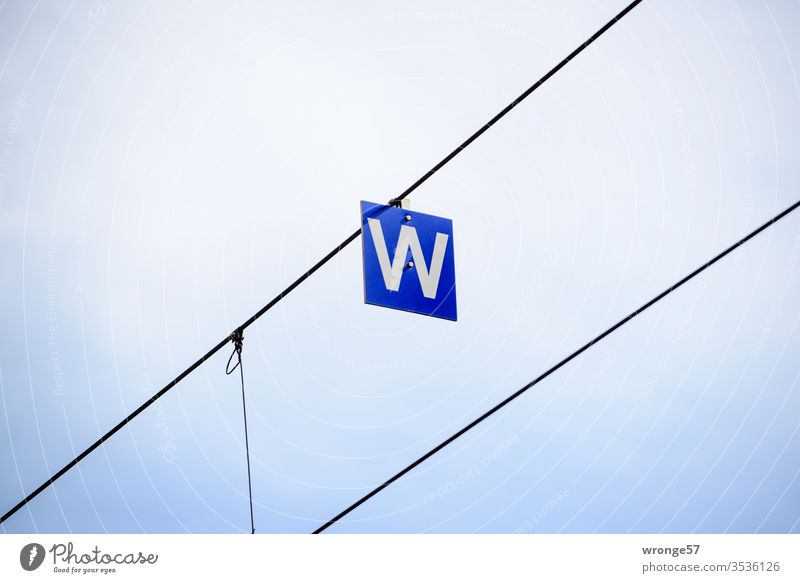 A white W on a blue board hanging from a wire letter White Blackboard sign Signs and labeling Exterior shot Deserted Colour photo Characters Letters (alphabet)