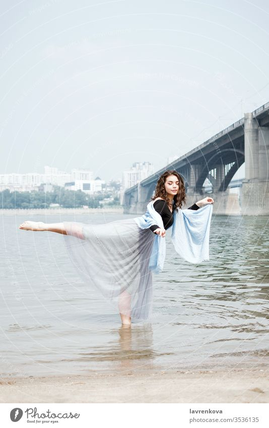 Young adult white female woman on a beach doing arabesque in the water, selective focus dancer movement beautiful aesthetic lifestyle dress nature sea