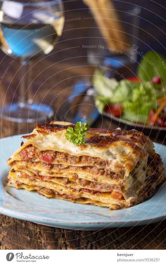 Portion of fresh lasagne on a plate Lasagne Evening grissini Summer Vine White wood Rustic Lettuce Meat Minced meat Slice Delicious herbs Bolognese Bolognaise