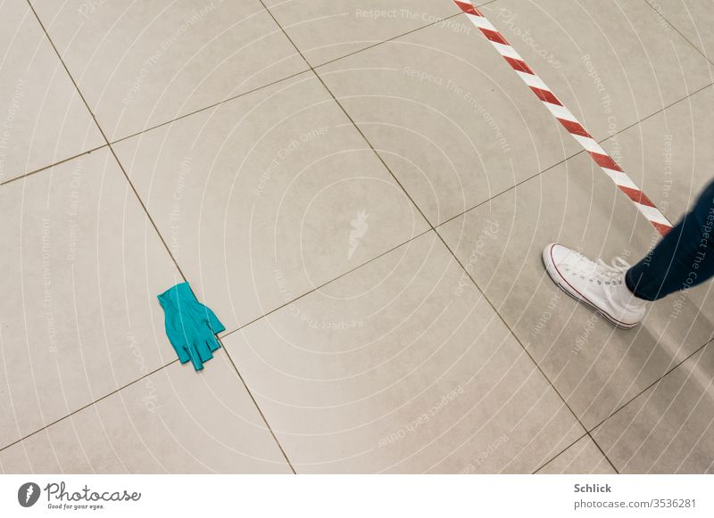 Coronakrise tiled floor with thrown away disposable glove Distance marker and leg of a passer-by corona crisis Ground tiles Lie Throw away distance marking
