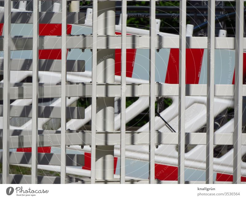 Red and white barriers behind a white metal fence cordon Barrier Protection Safety Fence Exterior shot Border Metal Structures and shapes Deserted Colour photo