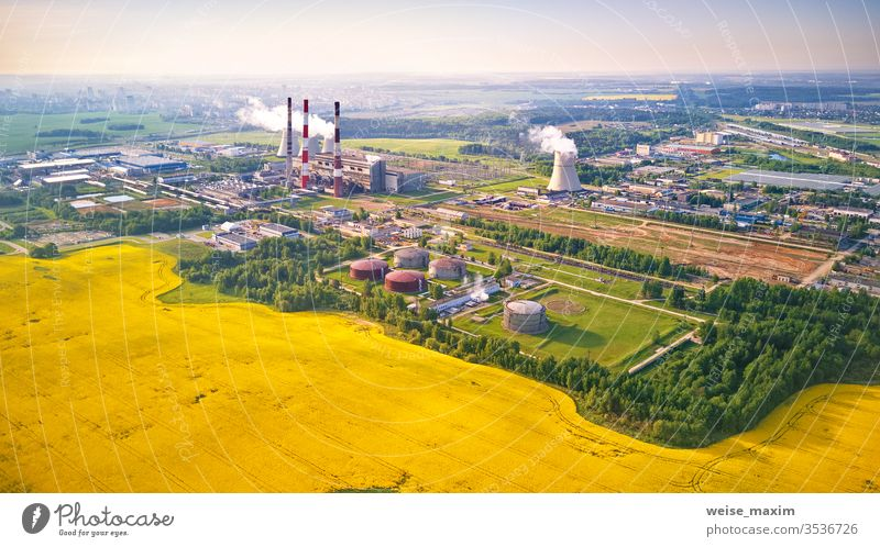 aerial view of power plant with flowering colza field nuclear station industry cooling atomic rapeseed canola tower energy spring drone cooler construction
