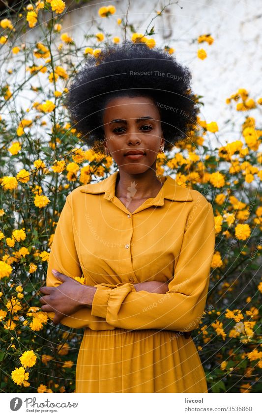young african american woman in yellow dress enjoying a garden with yellow flowers black woman girl people portrait lifestyle cool lovely outdoor exterior