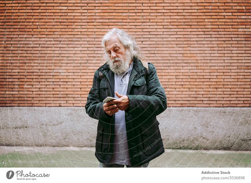 Male hipster using mobile phone near brick wall senior man smartphone city serious street male elderly aged gray hair long hair masculine handsome camera casual