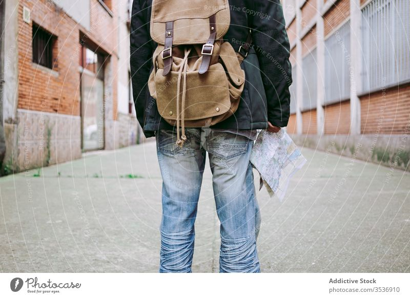 Crop male tourist walking with backpack and map in street man travel traveler trip journey stroll lifestyle destination town navigate adventure route vacation