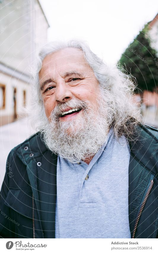 Cheerful old man with grey hair and long beard looking at camera cheerful happy senior traveler wisdom street portrait city pensioner town trip glad joy holiday