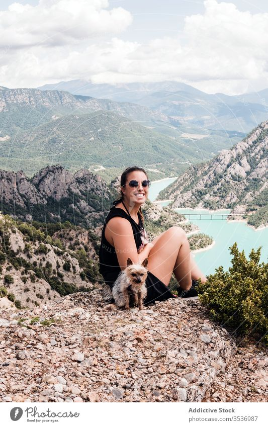 Anonymous female tourist with dog sitting on hill and enjoying landscape woman summer trip scenery nature vacation rest pet sunglasses black picturesque journey