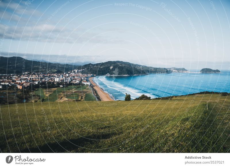 Picturesque view from green hill of seashore and town on sunny day in Spain valley landscape nature coast sky spain picturesque peaceful calm countryside