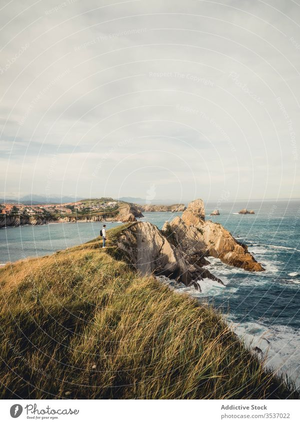 Male traveler standing on rocky seashore in summer in Spain view man photo camera backpack seascape nature trip vacation coast spain rest picturesque landscape