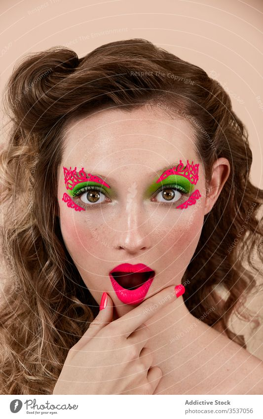 Amazed woman with bright makeup colorful amazed concept style rub chin mouth opened model young female appearance astonish surprise vivid vibrant trendy gesture