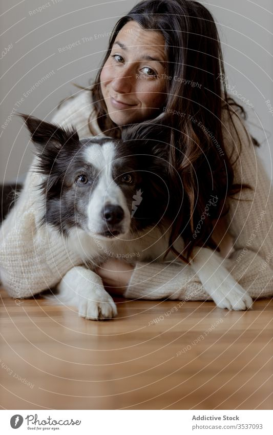 Happy woman embracing cute purebred gray white dog during rest on floor embrace hug care friendship pet adorable border collie together animal happy smile