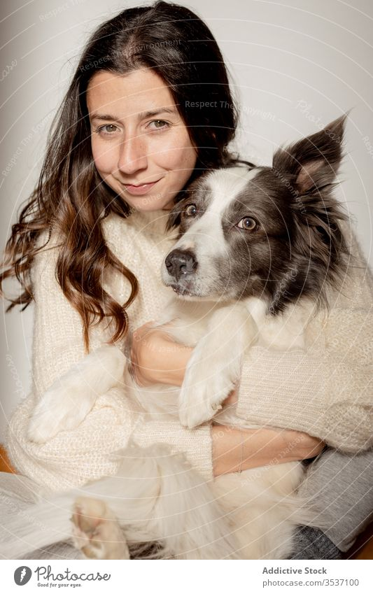 Happy woman embracing cute purebred gray white dog during rest on floor embrace hug care sit friendship pet adorable border collie together animal happy smile