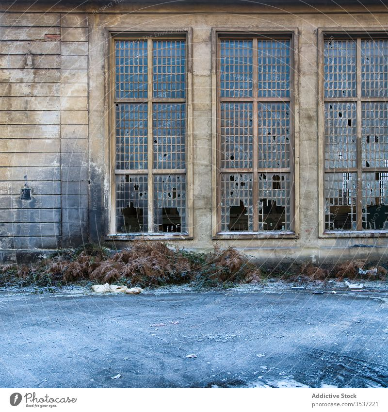 Old industrial building with broken windows abandoned wall shabby weathered ruin stone grid glass nobody neglect messy crash hole crisis uninhabited exterior
