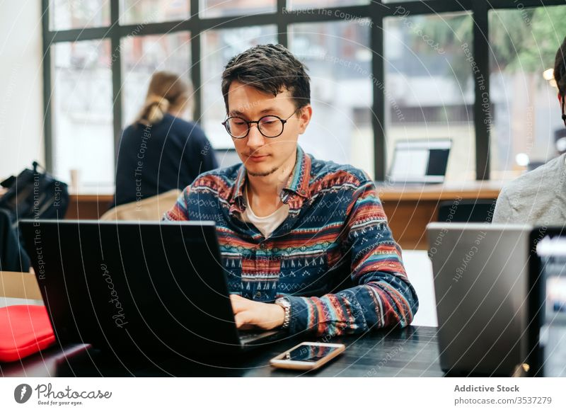 Focused worker using laptop in office man typing intelligent workplace professional workday smartphone project eyeglasses casual desk computer employee internet