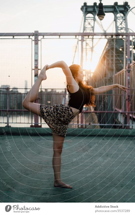 Tranquil woman doing yoga on bridge practice cityscape flexible asana lord of dance pose tranquil female urban scenery casual outfit skirt exercise natarajasana