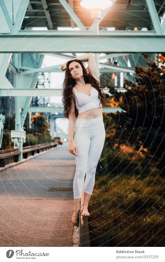 Serene woman in sportswear standing on sidewalk curb in city grace pavement balance serene slim evening female tranquil quiet calm long hair top bra leggings