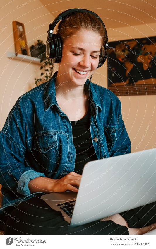 Cheerful young woman using laptop in light bedroom at home headphones read surfing social media watch relax chill listen search lounge check joy rest browsing