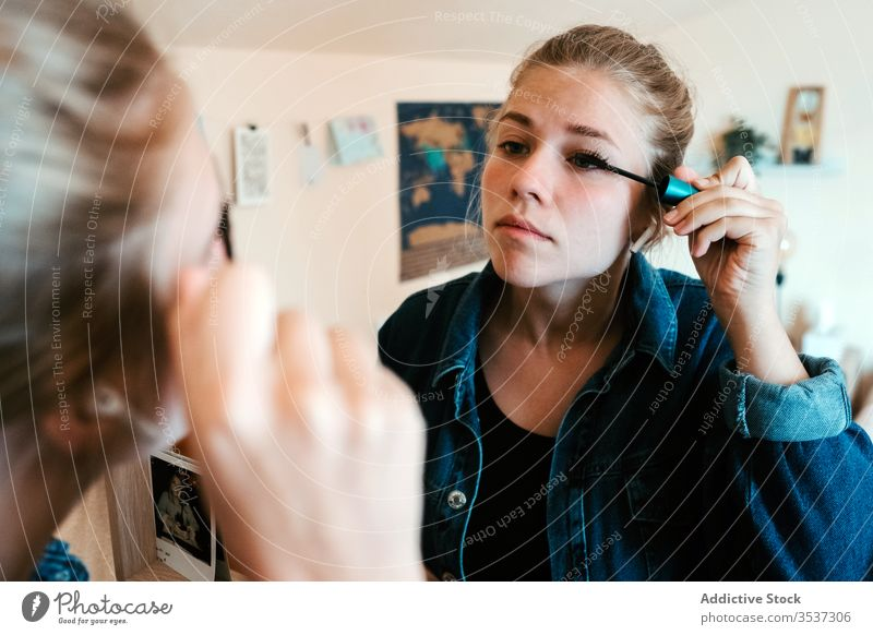 Young woman applying makeup to eyes in light bedroom at home mascara reflection mirror eyelashes make up cosmetic visage brush face female apartment appearance