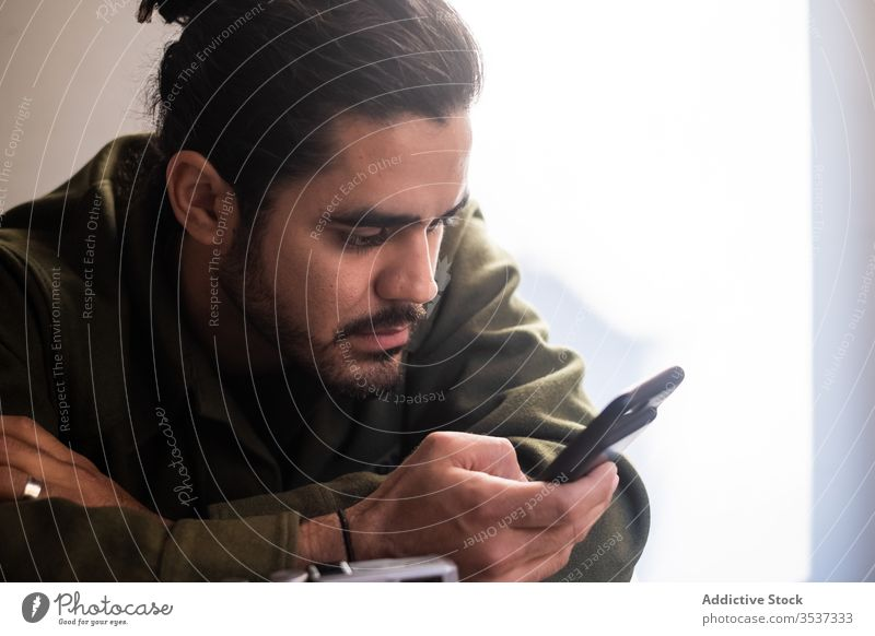 Serious man using smartphone in light room beard browsing surfing pensive handsome message ethnic mobile gadget communicate casual internet connection