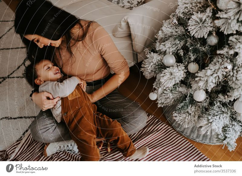 Cheerful loving mother hugging little son sitting on floor near Christmas tree cuddle christmas home playful cozy holiday smile child together kid parent