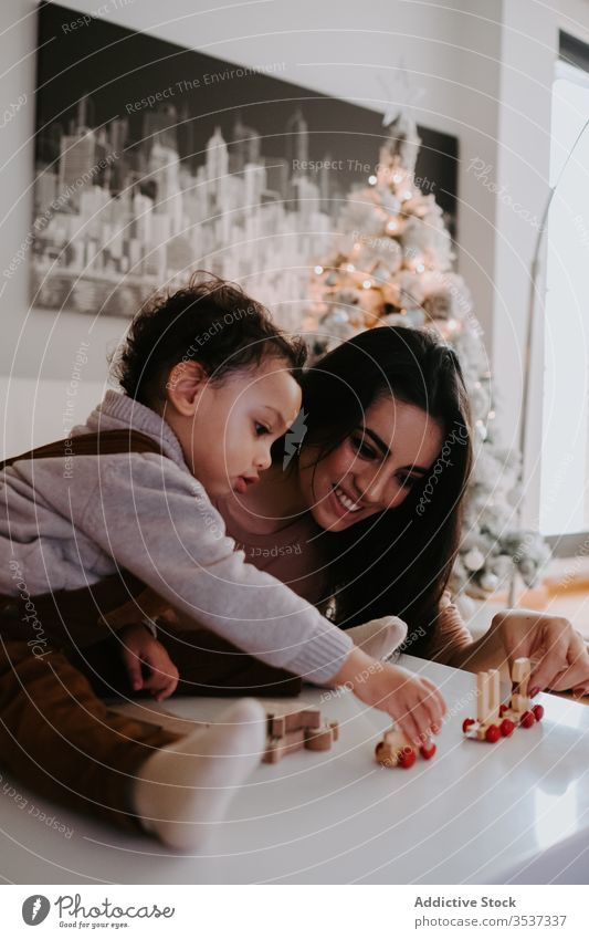 Mother and son playing with wooden toys on table mother home bonding cozy upbringing preschool parent kid cheerful fun woman boy smile game childhood ethnic