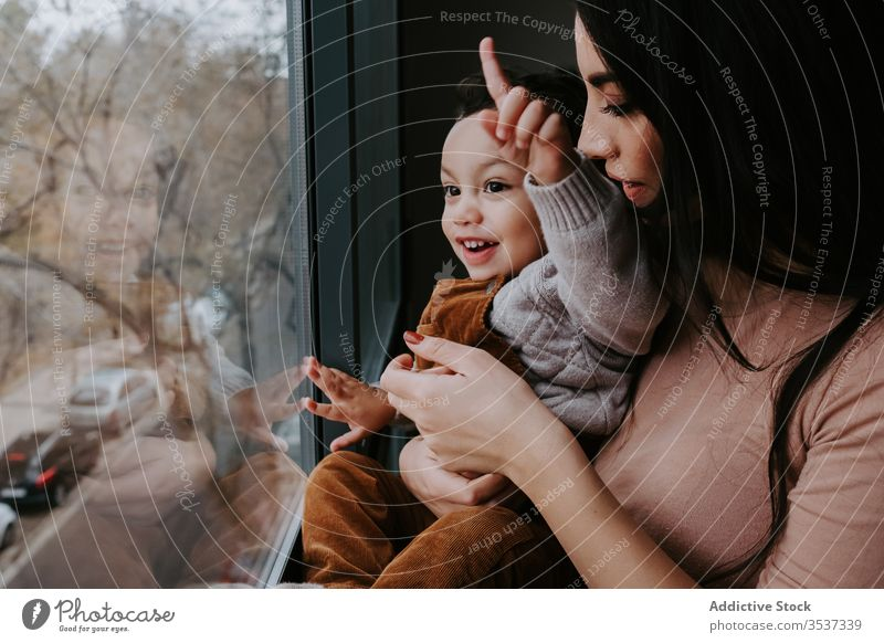 Positive young mother and little son standing near window and admiring view home curious explore point content excited cute child smile embrace kid parent