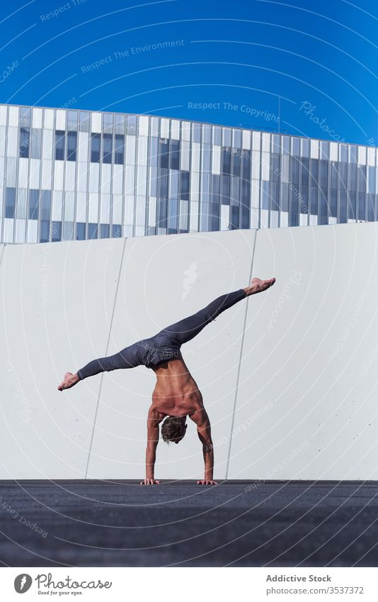 Male acrobat doing handstand on rooftop shirtless man urban upside down distant exercise stretch balance muscular perform strong modern architecture sportsman