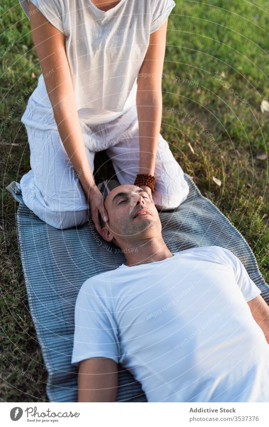 Relaxed couple meditating on green grass yoga meditate lying mat together eyes closed harmony meadow calm pose field spiritual massage white lawn summer tree