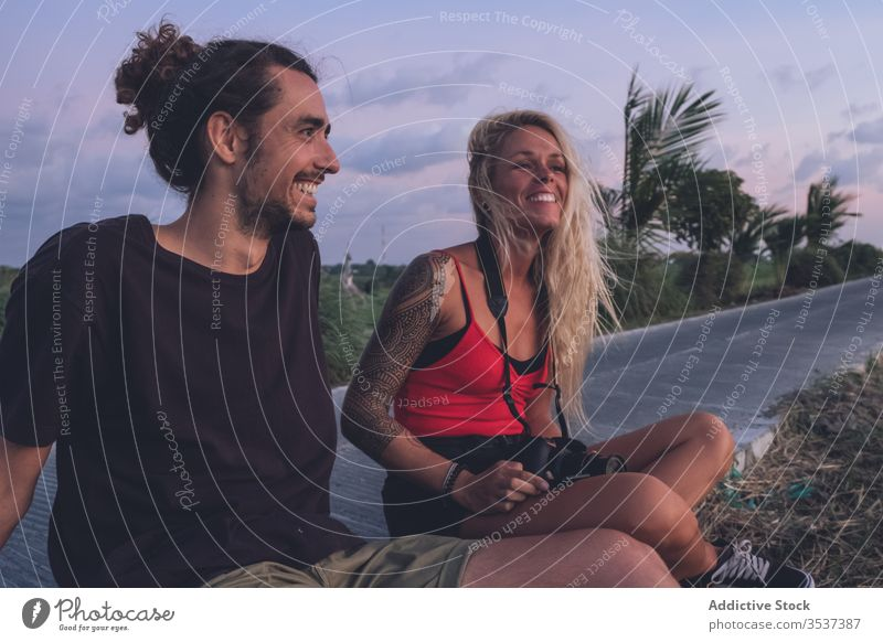 Delighted couple enjoying sunset during vacation evening traveler hipster roadside tropical sundown delight freedom inspiration content cheerful smile positive