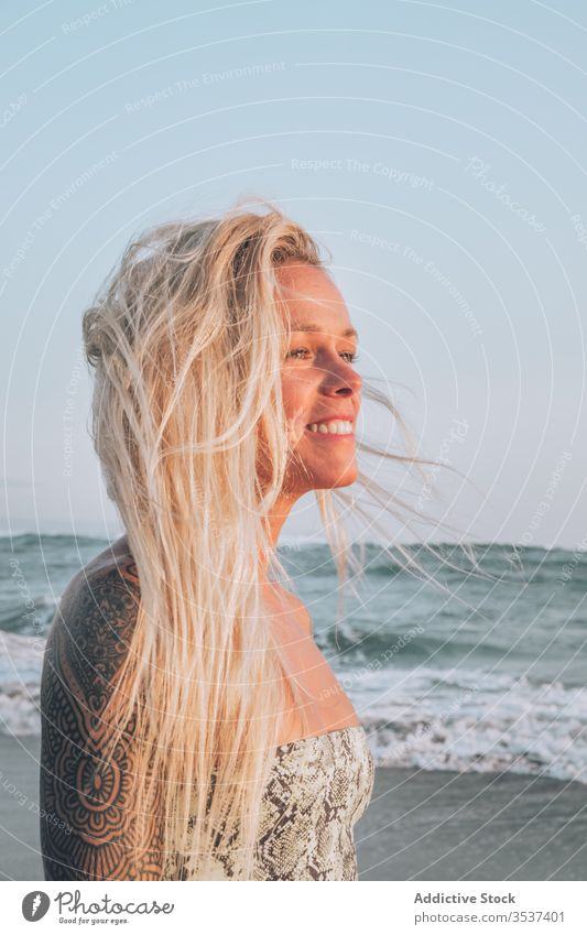 Smiling young blonde resting on seashore during sunny day woman beach shoulder tattoo summer sand vacation ocean relax coast nature travel happy leisure seaside