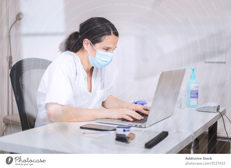 Young female doctor in medical mask working on laptop in clinic woman uniform glove desk serious hospital professional covid 19 coronavirus pandemic outbreak