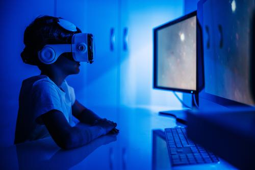 Unrecognizable boy in VR headset sitting in front of computer vr desktop monitor entertainment video using device gadget glasses wireless watch screen