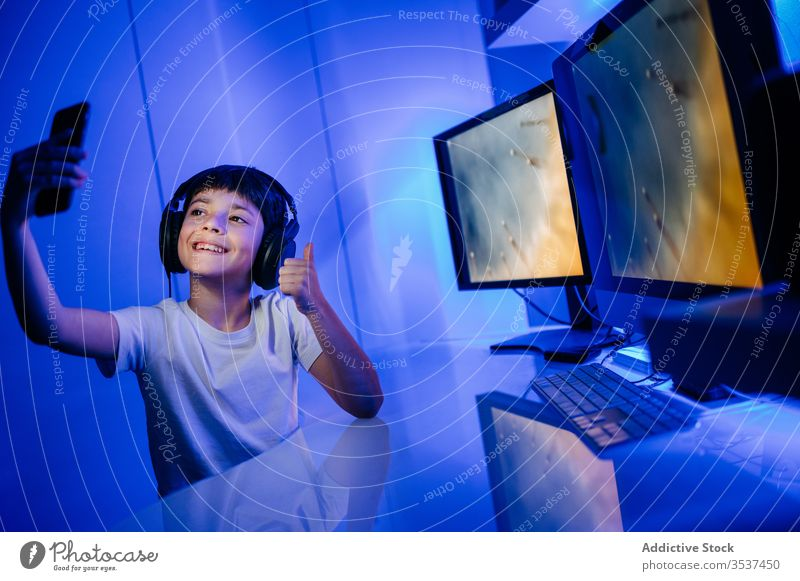 Cheerful boy in headset taking selfie on smartphone at home headphones thumb up toothy smile desktop computer using gadget device mobile phone cellphone monitor