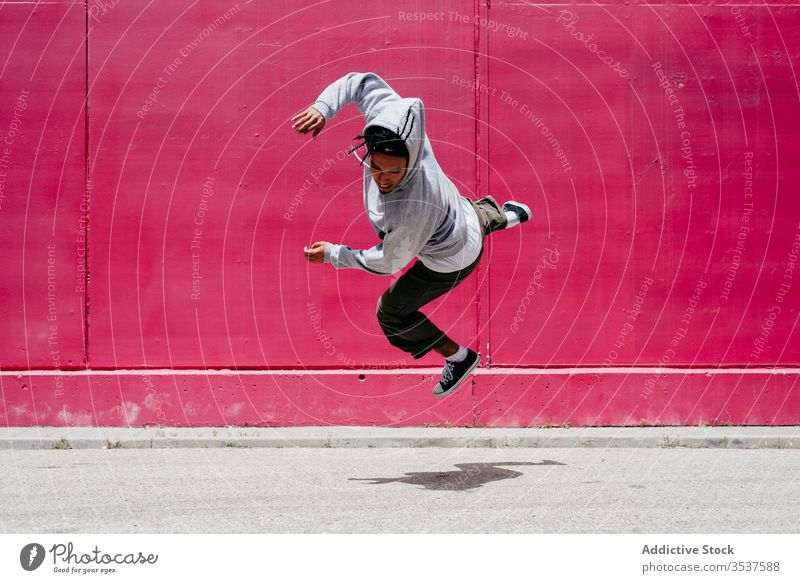 Young hispanic men jumping near to a pink wall on the street urban dance lifestyle city posing standing colorful daylight mixed hat hip-hop cool modern male