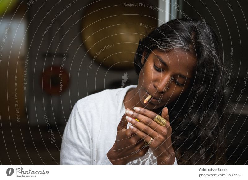 Ethnic woman smoking weed on terrace smoke marijuana relax enjoy roll up young cigarette female ethnic indian hindu casual outfit apparel eyes closed stand dope
