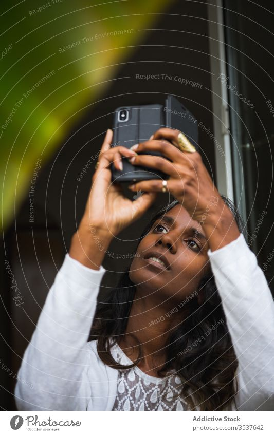 Concentrated Indian woman taking photo on smartphone take photo plant balcony concentrate camera mobile using female ethnic indian hindu focus serious