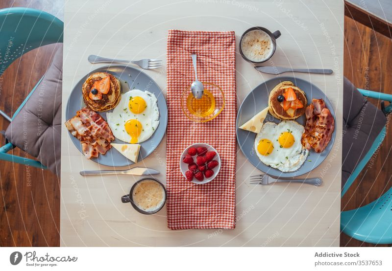 Delicious fried eggs with bacon and cheese for breakfast plate cupcakes strawberries black berries honey food serve meal pancake berry dish table nutrition