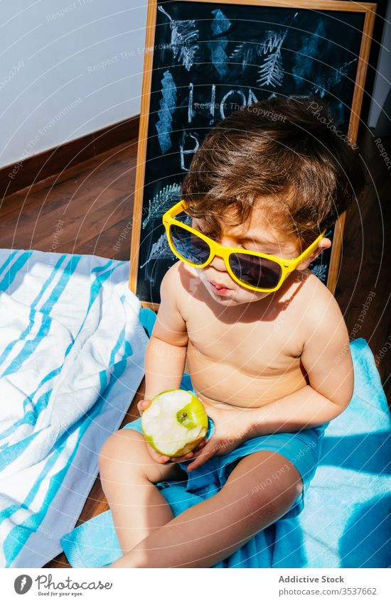 Happy little boy in sunglasses having beach at home dreaming of summer self isolation fun happy social distancing quarantine cheerful yellow blue playful