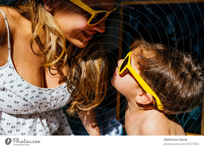 Positive mother playing with son in yellow sunglasses on sunny day home beach love dream together quarantine self isolation social distancing sunlight close