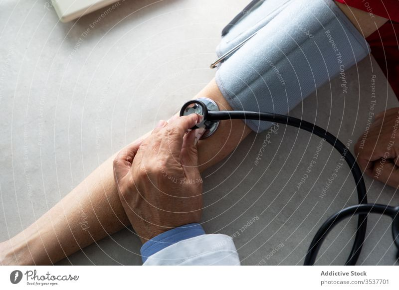Doctor measuring blood pressure of young patient in clinic doctor man measure stethoscope tonometer coronavirus outbreak physician hospital examine diagnostic