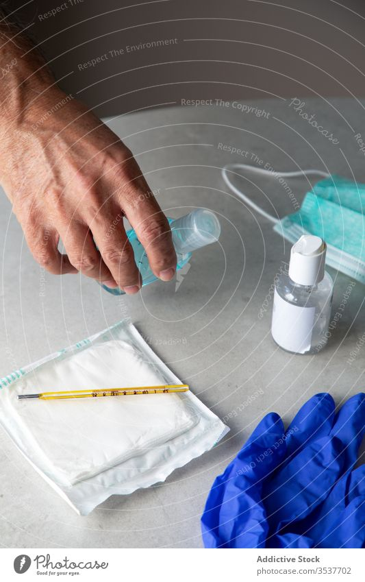 Crop male doctor applying hand sanitizer in medical room antiseptic man therapist coronavirus antibacterial protect outbreak treat disinfect sit table clinic