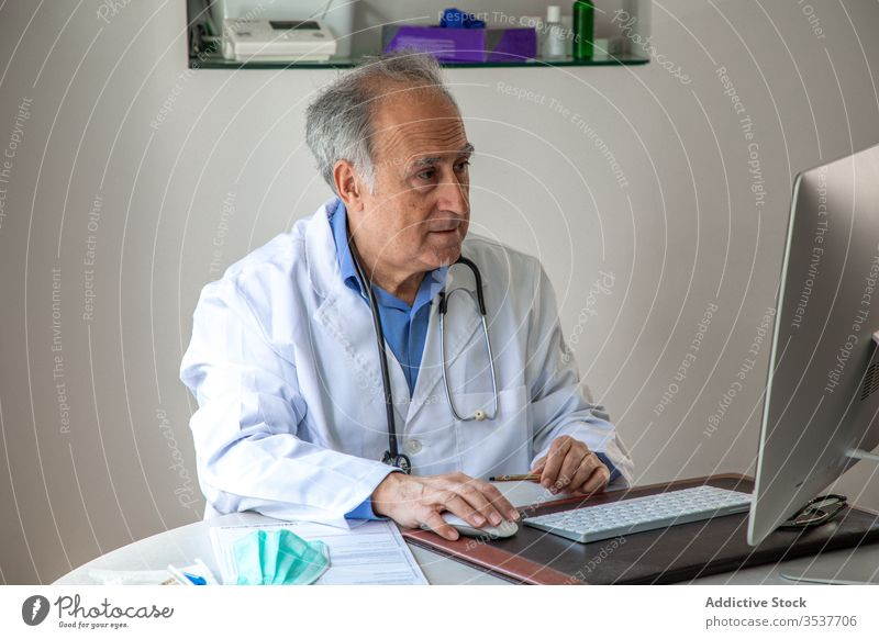 Elderly male physician conducting telemedicine consultation via laptop in clinic man elderly doctor telehealth outbreak using senior aged gray hair medical gown