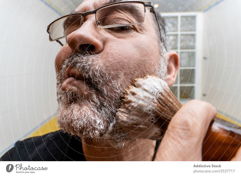 Man applying shaving foam with brush man shave prepare beard mature bathroom procedure hygiene grooming care male middle age routine treat tool morning home